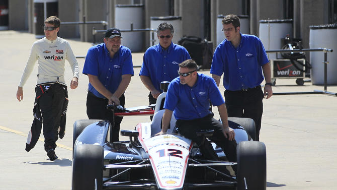 Will Power, left, of Australia, follows his car and crew from the garage during IndyCar testing at Texas Motor Speedway on Monday, May 7, 2012, in Fort Worth, Texas. (AP Photo/LM Otero)