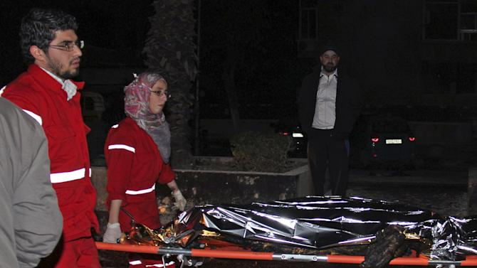 In this photo released by the Syrian official news agency SANA on Thursday,  Jan. 3, 2013, Syrian Red Crescent workers carry a dead body from a gas station that was attacked by a car bomb killing several people, activists said, in Damascus, Syria. Syrian ground and air forces bombarded rebel strongholds on the outskirts of Damascus and other areas around the country Friday while anti-government forces targeted a military post near the capital with a car bomb, activists said. (AP Photo/SANA)
