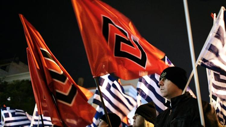 Member of the far right Golden Dawn party hold flags as they take part in a rally in Athens on February 1, 2014