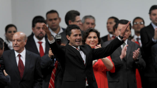 Mexico's President Enrique Pena Nieto, front, waves during a national convention of the Institutional Revolutionary Party (PRI), in Mexico City, Sunday,  March 3, 2013. Mexico's ruling party changed on Sunday its platform to allow a reform that could bring private investment into the state-owned oil monopoly, in a country where oil is a source of national pride. (AP Photo/Marco Ugarte)