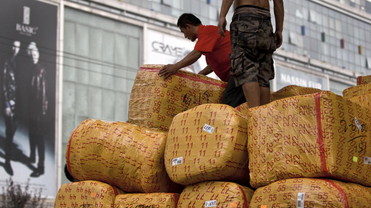 Workers load goods on a truck near a wholesale market for fashion clothing in Beijing Monday, Sept. 10, 2012. China's imports shrank unexpectedly in August in a sign its economic slump is worsening and the Chinese president warned growth could slow further, prompting expectations of possible new stimulus spending. (AP Photo/Andy Wong)