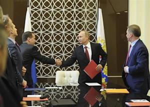 Russian President Vladimir Putin shakes hands with Prime Minister Dmitry Medvedev during a Security Council meeting in Sochi March 13, 2014. REUTERS/Mikhail Klimentyev/RIA Novosti/Kremlin