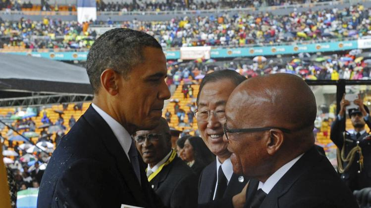 GCIS handout photo shows U.S. President Obama shaking hands with South African President Zuma at the Memorial Service for Nelson Mandela in Johannesburg
