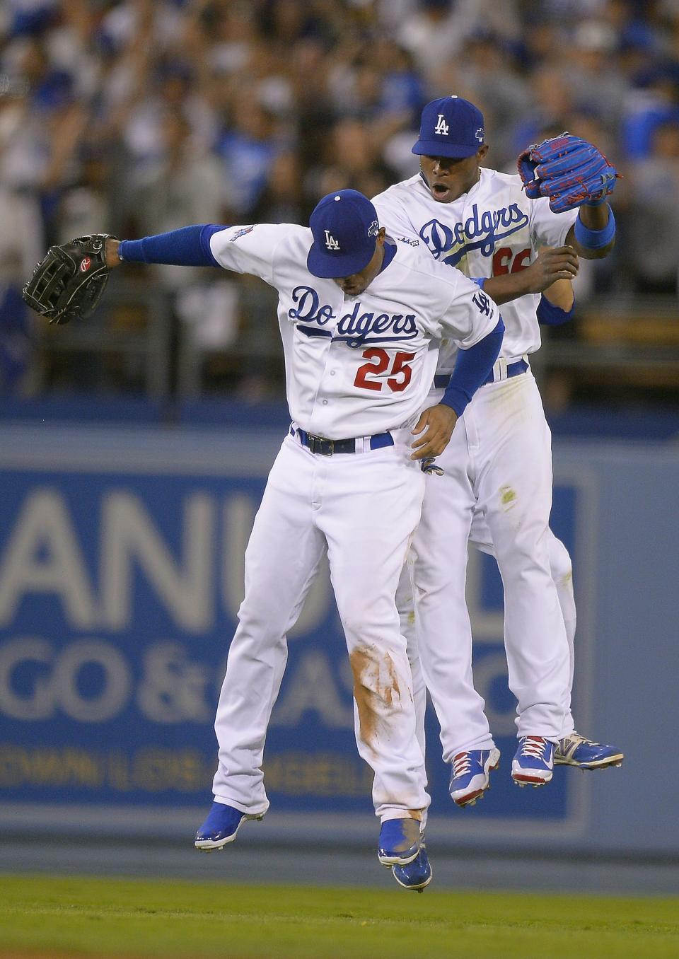 Los Angeles Dodgers' Carl Crawford (25) and Yasiel Puig celebrate after Game 3 of the National League baseball championship series against the St. Louis Cardinals Monday, Oct. 14, 2013, in Los Angeles. The Dodgers beat the Cardinals 3-0 and trail in the series 2-1. (AP Photo/Mark J. Terrill)