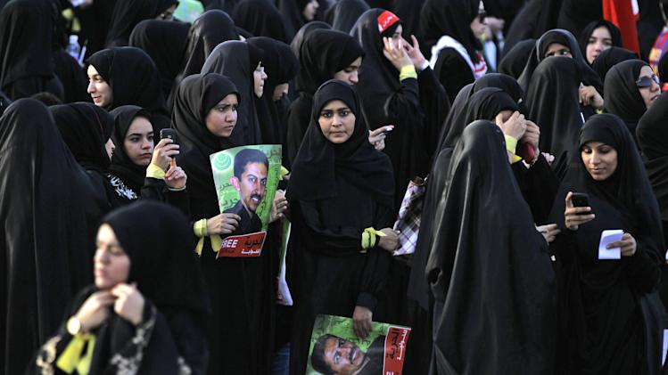 """Anti-government protesters hold pictures of jailed political leader Abdulhadi al-Khawaja, who has been on a hunger strike for more than 70 days, during a march through Jidhafs, Bahrain, on Tuesday, April 24, 2012. Witnesses said police in Bahrain have used tear gas and water cannons to disperse hundreds of protesters calling for al-Khawaja's release.The Arabic on the pictures reads: """"Freedom for al-Khawaja.""""  (AP Photo / Hasan Jamali)"""