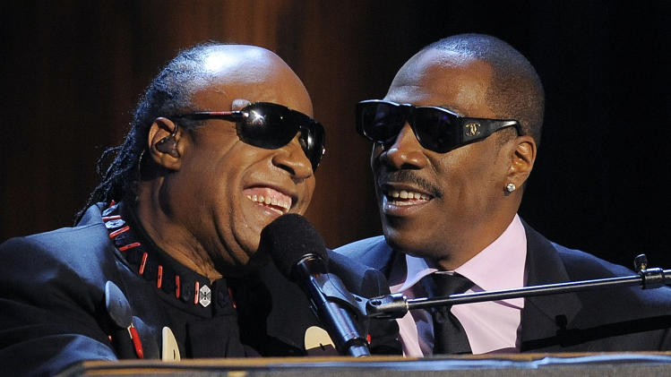 "Stevie Wonder, left, is joined by Eddie Murphy to sing Wonder's song ""Higher Ground"" onstage during ""Eddie Murphy: One Night Only,"" a celebration of Murphy's career at the Saban Theater on Saturday, Nov. 3, 2012, in Beverly Hills, Calif. (Photo by Chris Pizzello/Invision)"