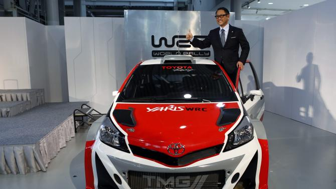 """Toyota Motor Corp President Akio Toyoda poses for pictures on the top of the """"Yaris WRC"""", a vehicle being developed for the FIA World Rally Championship (WRC) during a news conference to announce its return to WRC in 2017, in Tokyo"""