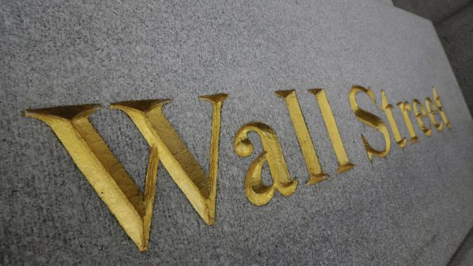 FILE - In this Oct. 2, 2014, file photo, Wall Street is etched in the facade of a building in New York's Financial District. The U.S. stock market is opening sharply lower, Tuesday, Jan. 27, 2015, following disappointing corporate earnings and weak economic news. (AP Photo/Richard Drew, File)