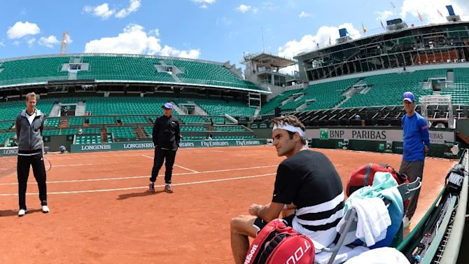 Swiss player Roger Federer (2ndR) and Swedish coach Stefan Edberg (L) take a break during a training session prior the 2015 French Open Tennis championships at the Roland Garros stadium in Paris on May 20, 2015
