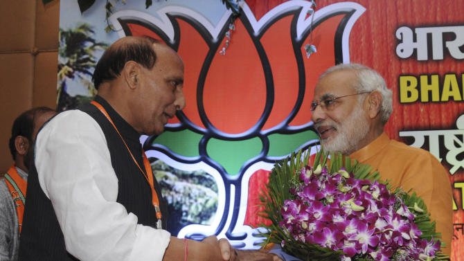 Chief Minister of India's western state of Gujarat Narendra Modi, right, is greeted by Bharatiya Janata Party (BJP) President Rajnath Singh during the BJP's national executive meeting at Panaji, Goa, India, Sunday, June 9, 2013. Party symbol Lotus is seen in the background. India's main opposition party BJP announced Sunday that Narendra Modi, a deeply divisive Hindu ideologue will head its 2014 election campaign, indicating he would be its choice for prime minister if the party were to win. (AP Photo)