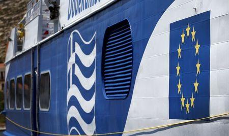 The EU flag and Greece's national flag are seen on the side of a cruise ship in the village of Meyisti on the Island of Kastellorizo