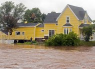 A resident looks on as dikes on the Salmon River gave way in Truro, Nova Scotia on Monday, Sept. 10, 2012. The area is under a rainfall warning as Tropical Storm Leslie churns toward Atlantic Canada. Leslie is expected to make landfall in Newfoundland bringing heavy rain and high winds. (AP Photo/The Canadian Press, Andrew Vaughan)