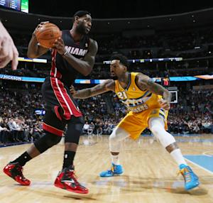 Miami Heat forward LeBron James, left, works the ball inside as Denver Nuggets forward Wilson Chandler defends in the first quarter of an NBA basketball game in Denver on Monday, Dec. 30, 2013. (AP Photo/David Zalubowski)
