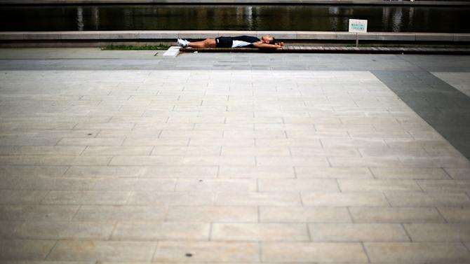 A man takes a nap under scorching heat in Tokyo, Saturday, July 12, 2014.