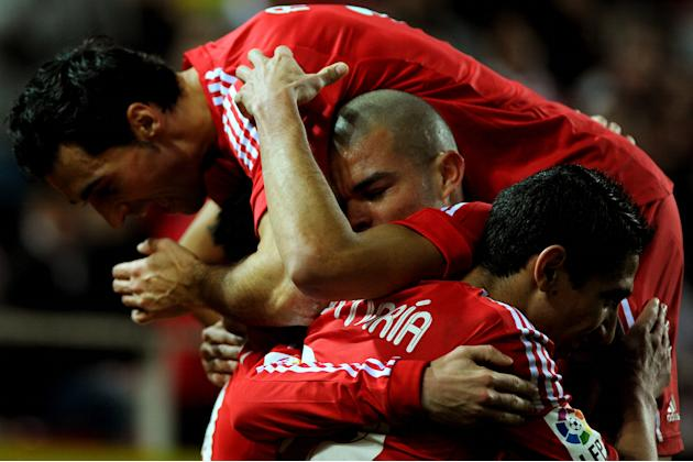Real Madrid's midfielder Jose Maria Callejon (L) celebrates with teammates after scoring during their Spanish league football match Sevilla FC vs Real Madrid on December 17, 2011 at Ramon Sanchez Pizj