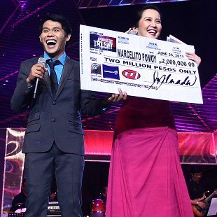 Marcelito Pomoy with judge Kris Aquino holding a replica of his P2-M check. (Jerome Ascano, NPPA Images)