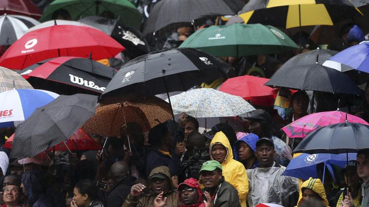 People sing at the First National Bank (FNB) Stadium during the national memorial service for former South African President Nelson Mandela in Johannesburg