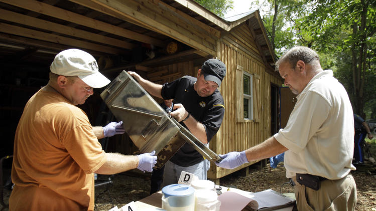 FILE - In this Sept. 2, 2010 file photo, Franklin County Detective Jason Grellner, center, sorts through evidence with Detective Darryl Balleydier, left, and reserve Officer Mark Holguin during a raid of a suspected meth house in Gerald, Mo.  Methamphetamine lab seizures are on the rise in the nation's cities and suburbs, raising new concerns about a lethal drug that has long been the scourge of rural America. (AP Photo/Jeff Roberson, File)