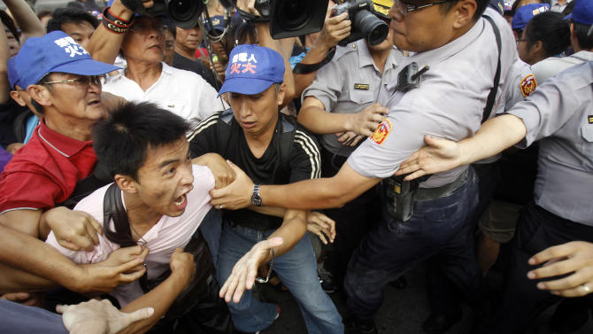In this photo taken Monday, Sept. 10. 2012, groups of laborers scuffle with police during a protest against Taiwanese President Ma Ying-jeou and his government's laws that allow companies that file for bankruptcy to refuse payments and pensions to employees in front of the presidential office in Taipei, Taiwan. Taiwan, in stark contrast to China, shrugged off authoritarian rule and underwent a transition over the past two decades to complete democracy, with sometimes-rowdy elections and a thriving civil society. (AP Photo/Wally Santana)
