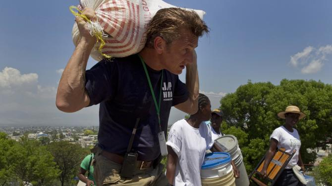 FILE - In this April 10, 2010 file photo, U.S. actor Sean Penn carries the belongings of a person displaced by the earthquake as people are relocated from the Petion ville Golf Club to a new camp, Corail-Cesselesse, in Port-au-Prince, Haiti.  Penn is being honored by a group of Nobel laureates for his relief work in Haiti following the country's devastating January 2010 earthquake. Penn is to receive the 2012 Peace Summit Award at the 12th World Summit of Nobel Peace Laureates at an event in Chicago in April 2012 and is expected to draw such luminaries as Poland's Lech Walesa and the Dalai Lama. (AP Photo/Ramon Espinosa, File)