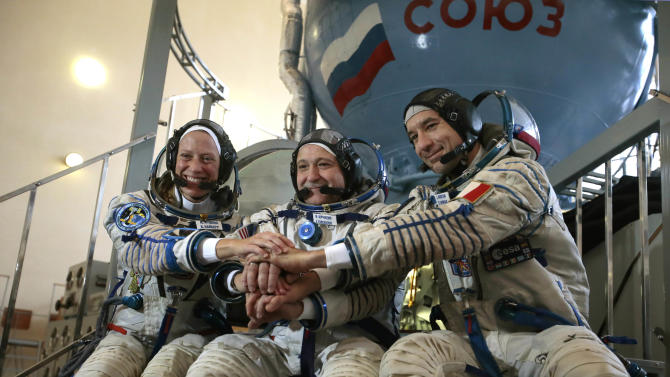U.S. astronaut Karen Nyberg, left, Russian cosmonaut Fyodor Yurchikhin, center, and European Space Agency astronaut Luca Parmitano pose for the media before their final preflight practical examination in a mock-up of a Soyuz TMA space craft at the Russian Space Training Center in Star City outside Moscow, Russia on Tuesday, April 30, 2013. The three are scheduled to travel to the International Space Station from Baikonur Cosmodrom on a Russian made Soyuz TMA-09M space craft on May 29, 2013. NASA is paying $424 million more to Russia to get U.S. astronauts into space, and the agency's leader is blaming Congress for the extra expense. NASA announced its latest contract with the Russian Space Agency on Tuesday, April 30, 2013. The $424 million represents flights to and from the International Space Station aboard Russian Soyuz spacecraft, as well as training, for six astronauts in 2016 and the first half of 2017. (AP Photo/Mikhail Metzel)