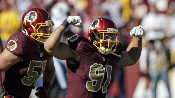 In this Oct. 19, 2014, file photo, Washington Redskins linebackers Ryan Kerrigan (91) and Will Compton (51) celebrate Kerrigan's sack during the second half of an NFL football game against the Tennessee Titans in Landover, Md. In contrast to, say, Robert Griffin III, Kerrigan is perhaps the most drama-free member of the Redskins. He leads the team with 7 and a half sacks, even though he's been playing hurt