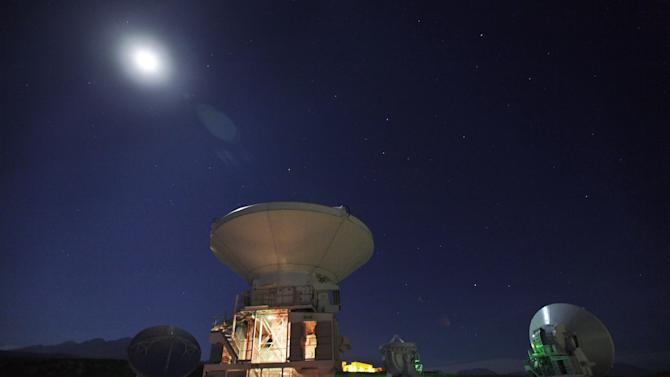 In this Sept. 26, 2012 photo, the moon shines over radio antennas at the operations support facility of one of the worlds largest astronomy projects, the Atacama Large Millimeter/submillimeter Array (ALMA) in the Atacama desert in northern Chile. Linked as a single giant telescope, the radio antennas pick up wavelengths of light longer than anything visible to the human eye and colder than infrared telescopes, which are good at capturing images of distant suns but miss planets and clouds of gases from which stars are formed. (AP Photo/Jorge Saenz)