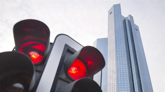 FRA606. Frankfurt/main (Germany), 13/12/2012.- (FILE) A file photo dated 13 December 2012 showing a red traffic light in front of the headquarters of the Deutsche Bank building in Frankfurt/Main, Germany. Analysts expect more losses for the final quarter of 2014 owing to set-asides for legal risks in figures due out 29 January 2015. That would be the fourth quarterly loss for joint directors Juergen Fitschen and Anshu Jain, who took over the reins of the bank in June 2012. Management plans to set out a more detailed strategy for the future in the second quarter of the year, but there is already speculation about the future of Postbank, a Deutsche Bank subsidiary. For now, there will be a teleconference with journalists where Fitschen and Jain will discuss preliminary results, with the annual press conference postponed until the business plan is ready. (Alemania) EFE/EPA/FRANK RUMPENHORST