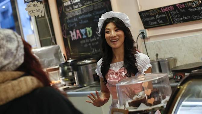 A waitress speaks with customers at the Maid Cafe New York