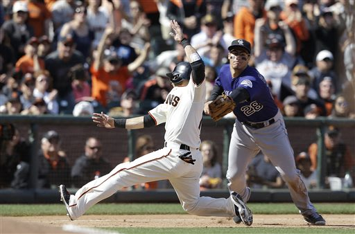 Colorado Rockies third baseman Nolan Arenado (28) tags out San Francisco Giants' Marco Scutaro sliding into third base during the eighth inning of a baseball game in San Francisco, Saturday, May 25, 2