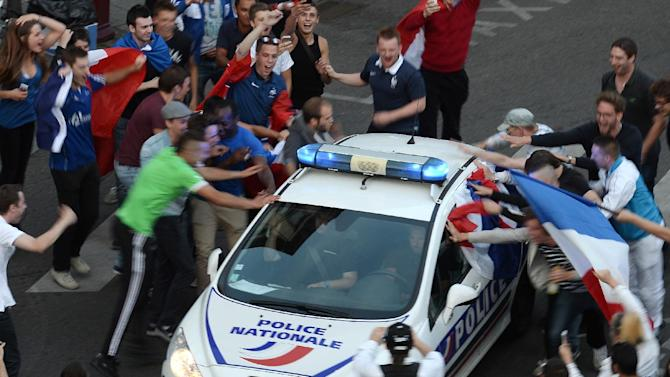 France supporters celebrate around a police car after the FIFA World Cup match against Nigeria on June 30, 2014 in Strasbourg, eastern France