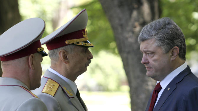 Ukrainian President Petro Poroshenko, right, meets with acting Ukrainian Defense Minister Mykhailo Koval, center, in Kiev, Ukraine, Wednesday, June 18, 2014. Ukraine's president said Wednesday that government forces will unilaterally cease fire to allow pro-Russian separatists in the east of the country a chance to lay down weapons or leave the country, a potential major development to bring peace to the country. (AP Photo/Mykhailo Markiv, pool)