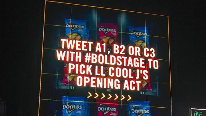 Fans participate in an interactive concert experience at the sixty-two-foot tall vending machine that doubled as the Doritos #Boldstage during the South by Southwest Music Festival, Thursday, March 14, 2013 in Austin, Texas.  (Photo by Erich Schlegel/Invision for Doritos/AP Images)