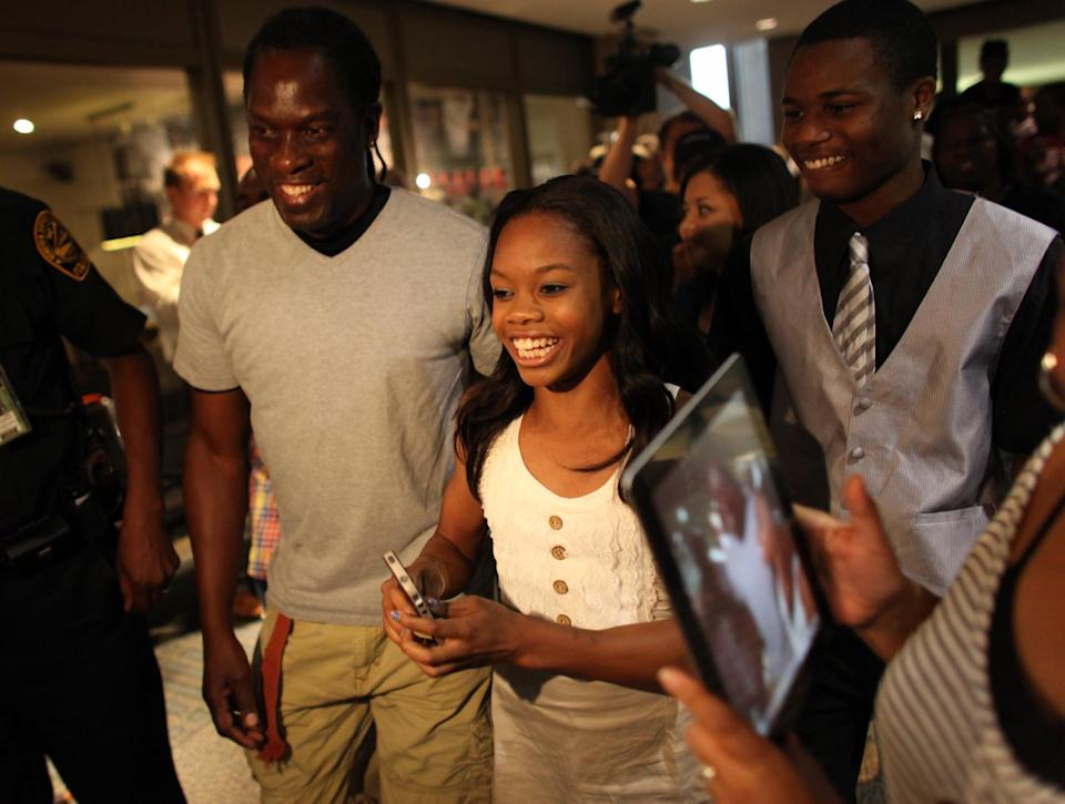 Greeted and accompanied by friends and family, 2012 Olympic gymnast and Gold medal winner Gabby Douglas arrives at the Norfolk, Va. Airport on Thursday evening, Aug. 16, 2012, on a visit to hometown of Virginia Beach, Va. (AP Photo/The Virginian-Pilot, Ross Taylor)