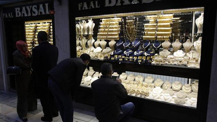 People look at gold jewelleries at a jewellery shop at the Grand Bazaar in Istanbul December 5, 2013. REUTERS/Murad Sezer