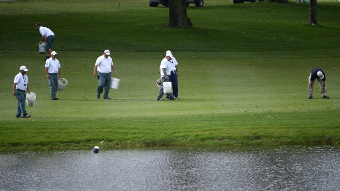 Work crews pick up debris on the eighth fairway after a severe thunderstorm passed through, causing a suspension of play, during the final round of the Arnold Palmer Invitational golf tournament in Orlando, Fla., Sunday March 24, 2013.(AP Photo/Phelan M. Ebenhack)