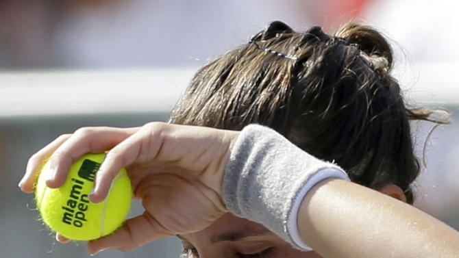 Andrea Petkovic, of Germany, wipes her forehead as she prepares to serve to Ekaterina Makarova at the Miami Open tennis tournament Monday, March 30, 2015, in Key Biscayne, Fla. (AP Photo/Alan Diaz)