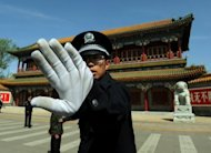 A Chinese policeman blocks photos being taken outside Zhongnanhai which serves as the central headquarters for the Communist Party of China in Beijing in April 2012. Chinese authorities are seeking to whitewash the alleged crimes of fallen leader Bo Xilai and protect his political backers by shifting the blame on his wife who will be tried for murder, activists say