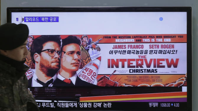 "A South Korean army soldier walks near a TV screen showing an advertisement of Sony Picture's ""The Interview,"" at the Seoul Railway Station in Seoul, South Korea, Monday, Dec. 22, 2014. North Korea hates the Hollywood film that revolves around the assassination of its beloved leader, but the country has had a long love affair with cinema _ of its own particular styling. (AP Photo/Ahn Young-joon)"