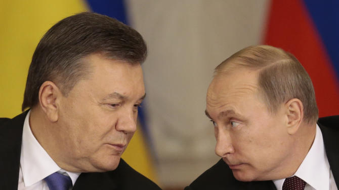 Russian President Vladimir Putin, right, and his Ukrainian counterpart Viktor Yanukovych chat during a news conference after their talks in Moscow on Tuesday, Dec. 17, 2013. Russian President Vladimir Putin says Moscow has agreed to sharply cut the price of its natural gas supplies to Ukraine and will buy $15 billion worth of Ukrainian government bonds, but says there was no discussion about Ukraine joining a free trade pact of three ex-Soviet nations. (AP Photo/Ivan Sekretarev)