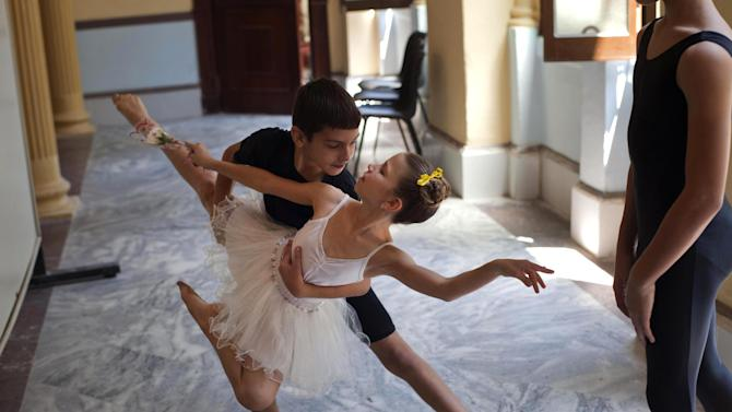 In this April 3, 2013 photo, young ballet students practice before a class at the National School of Ballet in Havana, Cuba.  The school, housed in a graceful building that occupies a full half-block in colonial Old Havana, not only teaches dance, but subjects like language, math and history. (AP Photo/Ramon Espinosa)