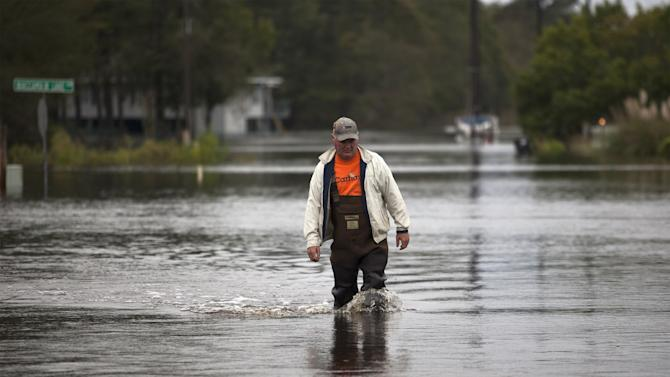 David Carroll of Waccamaw Lake Drive wades through the floodwaters in Conway