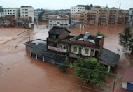 In this photo provided by China's Xinhua News Agency, streets are waterlogged in Gaoqiao township of Dongxing District in Neijiang, southwest China's Sichuan Province Sunday, July 22, 2012. On Sunday, the government warned of more storms over the following 24 hours for China's northeast, the port city of Tianjin east of Beijing, Inner Mongolia in the north, Sichuan and neighboring Yunnan province, and Guangdong and Hainan provinces in the southeast. (AP Photo/Xinhua, Lan Zitao) NO SALES