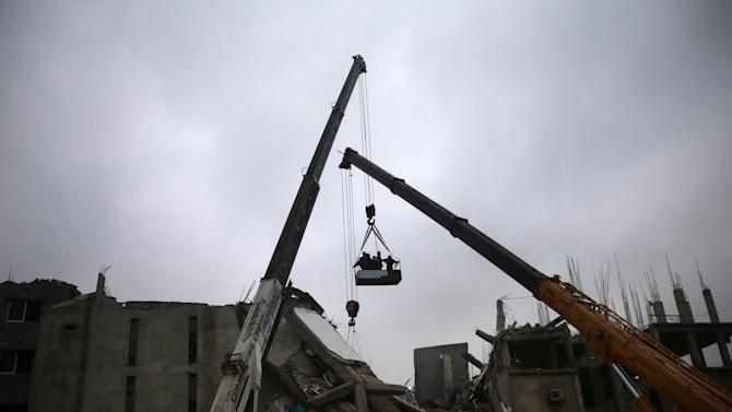 Fire fighters and army personnel are lifted by a crane for a visual survey of the garment factory building after it collapsed in Savar, near Dhaka, Bangladesh on Monday, April 29, 2013. Rescue workers in Bangladesh gave up hopes of finding any more survivors in the remains of a building that collapsed five days ago, and began using heavy machinery on Monday to dislodge the rubble and look for bodies - mostly of workers in garment factories there. At least 381 people were killed when the illegally constructed, 8-story Rana Plaza collapsed in a heap on Wednesday morning along with thousands of workers in the five garment factories in the building.(AP Photo/Wong Maye-E)