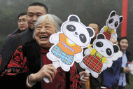 In this photo released by China's Xinhua News Agency, an elderly woman sees off the pandas in Ya'an, southwest China's Sichuan Province, Saturday, Dec. 3, 2011. As part of a ten-year joint research program, Tian Tian and Yang Guang, the pair of giant pandas, were set off for the Edinburgh Zoo from the Giant Panda Conservation and Research Center in Sichuan here on Saturday, Xinhua said. (AP Photo/Xinhua, Li Qiaoqiao) NO SALES