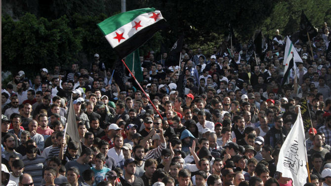 Supporters of Lebanese anti-Syrian regime and Salafist group leader Sheikh Ahmad al-Assir chant slogans and wave Syrian revolutionary flags during a protest against the Syrian regime in southern port city of Sidon, Lebanon, Sunday, Dec. 2, 2012. (AP Photo/Mohammed Zaatari)