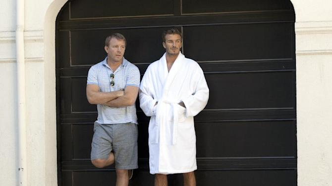 This October 2012 photo released by H & M shows soccer star David Beckham, right, and director Guy Ritchie on the set of Beckham's newest ad campaign for his bodywear collection in Los Angeles. The ad is more like a film short, directed by Guy Ritchie. Beckham stars as an action hero, saving the day in Los Angeles in his boxer briefs and bedroom slippers.  (AP Photo/H&M)