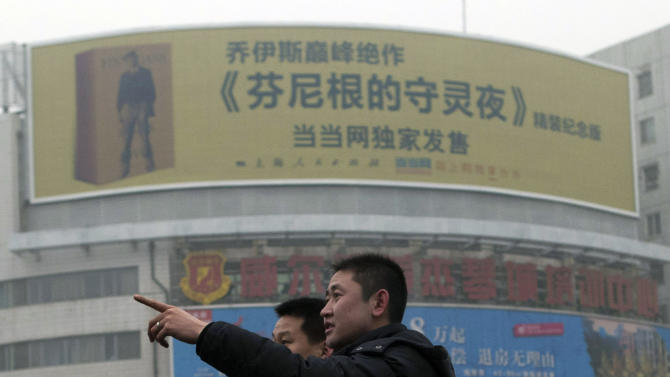 """A Chinese man points near a large billboard advertising the translated work of James Joyce's """"Finnegans Wake"""" on a street in Beijing, China, Wednesday, Jan. 30, 2013. The Chinese version is no easier to read than the original, the loyal-minded translator assures, but James Joyce's """"Finnegans Wake"""" has still sold out its initial run in China — with the help of some big urban billboards. The book, widely considered Joyce's most experimental and inscrutable work, was promoted by an unusual billboard campaign in major Chinese cities — with 16 of them in Shanghai alone. The official Xinhua News agency said it was the first time a book had been promoted that way in China. (AP Photo/Ng Han Guan)"""