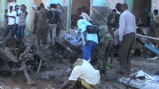 People and soldiers search in the rubble of a destroyed building on  February 28, 2016 in Baidoa after twin explosions in the Somali city killed at least 30 people