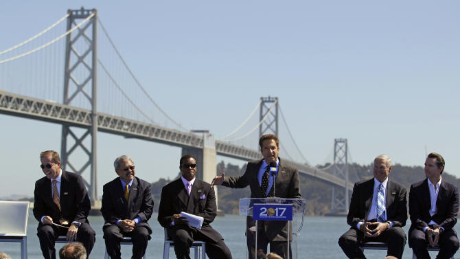 Golden State Warriors owner Peter Guber, at podium, gestures during an announcement in San Francisco, Tuesday, May 22, 2012, that the NBA basketball team wants to build a waterfront arena in San Francisco. The Warriors unveiled plans to build an arena at Piers 30-32. From left in the background are Warriors owner and CEO Joe Lacob, San Francisco Mayor Ed Lee, master of ceremonies Ahmad Rashad, Warriors executive Jerry West and California Lt. Gov. Gavin Newsom.  The Warriors unveiled plans to build an arena at Piers 30-32. The San Francisco-Oakland Bay Bridge is in the background. (AP Photo/Eric Risberg)
